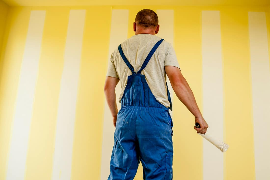 http://staging.mastermortgagebrokersydney.com.au - man in overalls with piant roller painting a room