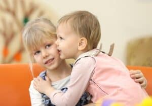 2 year old baby girl hugging her blond 7 to 8 year old sister