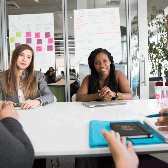 Two young woman in an office business meeting