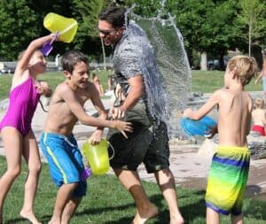 Young dad with his 3 young kids having a summer water fight at the park