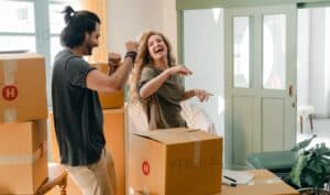Young man and woman laughing while unpacking boxes from their house move