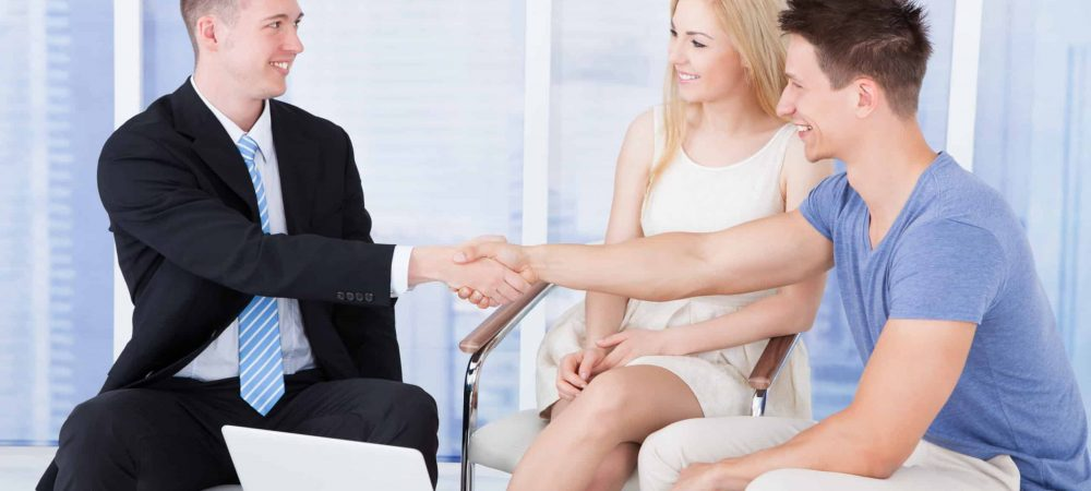 Young Couple Shaking Hands With Finance Broker